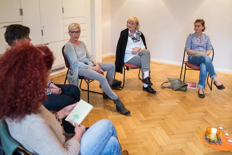 Mehrere Ehrenamtliche sitzen in einem Stuhlkreis und unterhalten sich